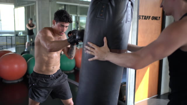 Man boxer punching combat bag with trainer