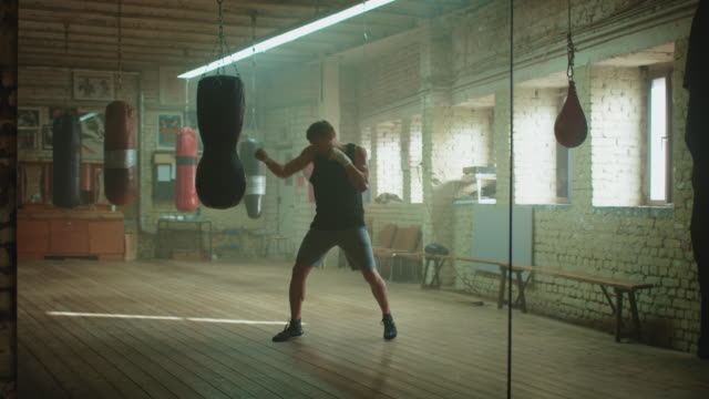 Man boxing punshing bag video