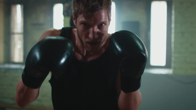 Man boxing punshing bag Muscular man boxing punshing bag in a old gym. He does his training and wears boxing gloves. There is some haze in the air. Its a pov shot of the bag. hd format stock videos & royalty-free footage