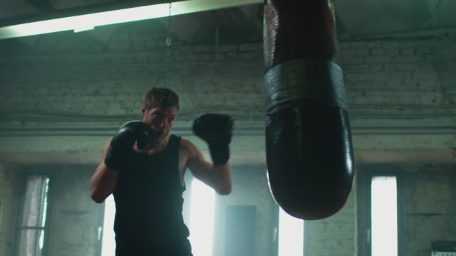 man boxing punshing bag - sacco per il pugilato video stock e b–roll
