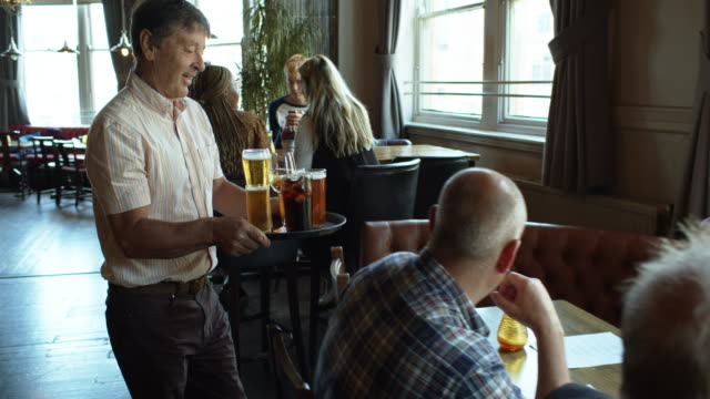 man bringing tray of drinks to friends at table in pub - england stock videos & royalty-free footage