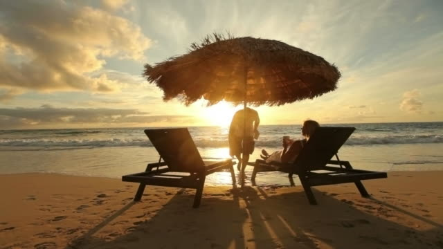 Man brings drink to woman sitting by beach at sunrise