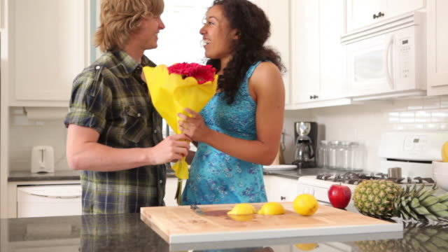 Man brings flowers to woman in kitchen video