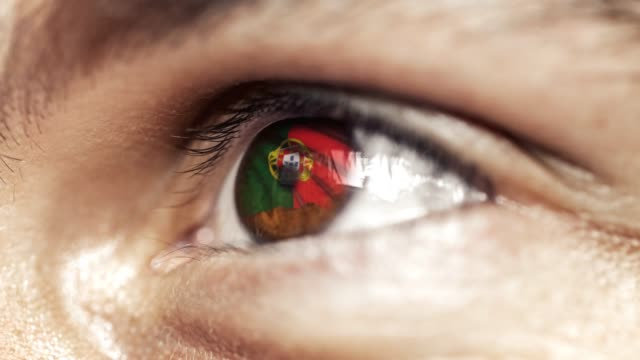 vídeos de stock e filmes b-roll de man brown eye in close up with the flag of portugal in iris,  with wind motion. video concept - portugal