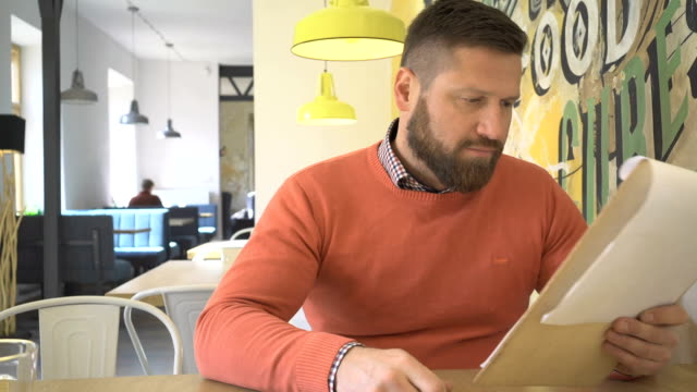 Man, browsing menu, lunchtime, sitting in cafe, steadicam Man, browsing menu, lunchtime,  in pub, he is sitting at table in cafe. Man is young, has beard and he is dressed in orange sweater, steadycam menu stock videos & royalty-free footage