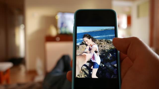 mann, die fotos auf seinem smartphone durchsuchen - online dating stock-videos und b-roll-filmmaterial