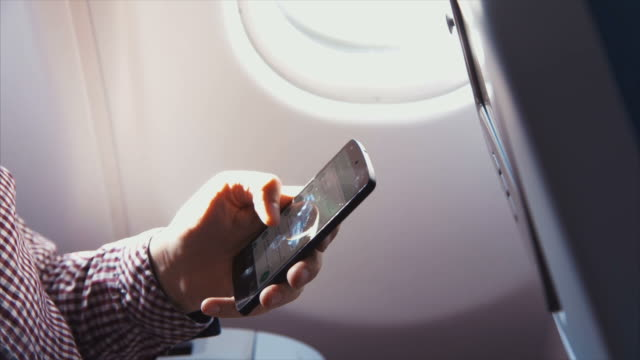Man browsing smart phone on the airplane (slow motion) - Vidéo