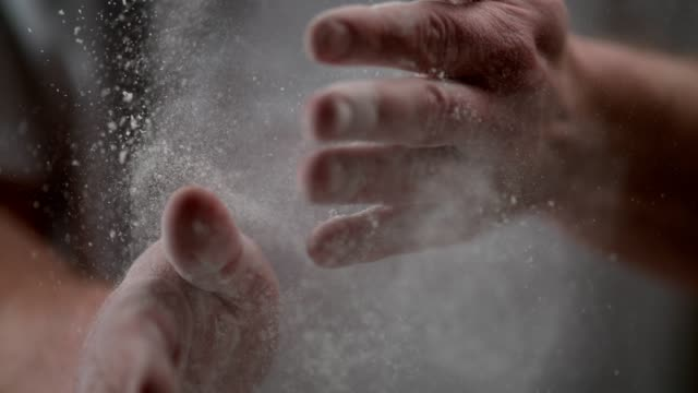 man brushes off hands from the flour. baking. super slow motion - battere le mani esprimere a gesti video stock e b–roll
