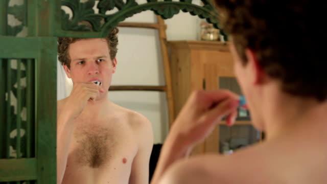 Man brushing teeth in front of mirror video