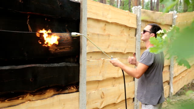 Man burns the surface of the wooden fence. video
