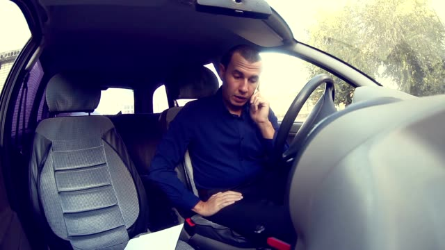 man businessman manager in the car talking on phone talks conviction video