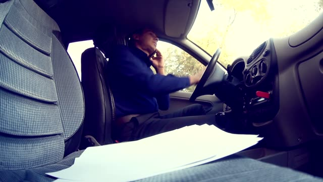 man  businessman talking on the phone in car keeps documents insurance business negotiations video