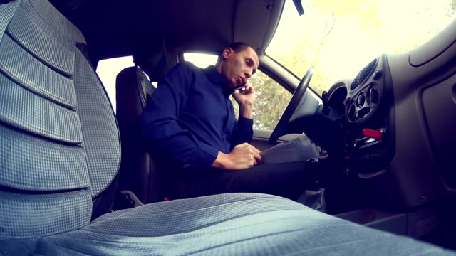 man businessman talking on the phone in the car keeps documents insurance business negotiations video