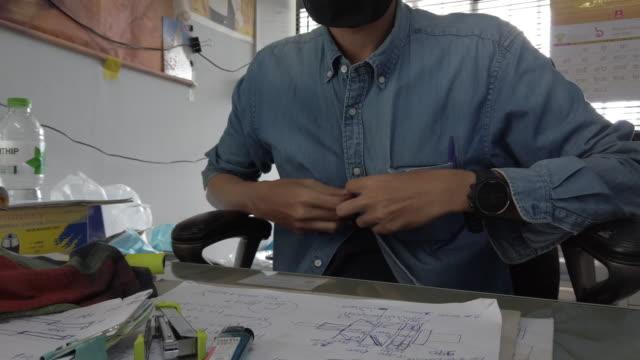 オフィスでシャツをボタンで押す4kの男 - 着る点の映像素材/bロール