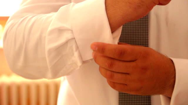 man buttoning shirt video