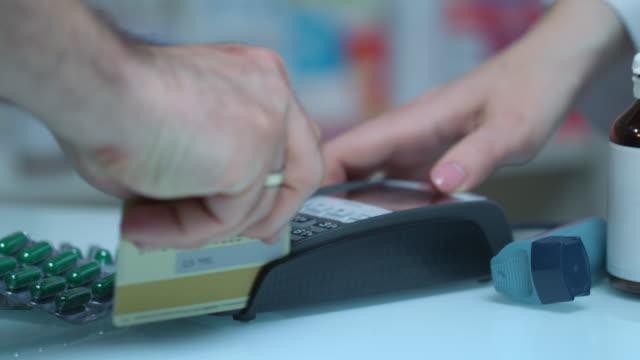 vidéos et rushes de homme acheter medicament avec carte terminal à la pharmacie. pos terminales au magasin médical - main service