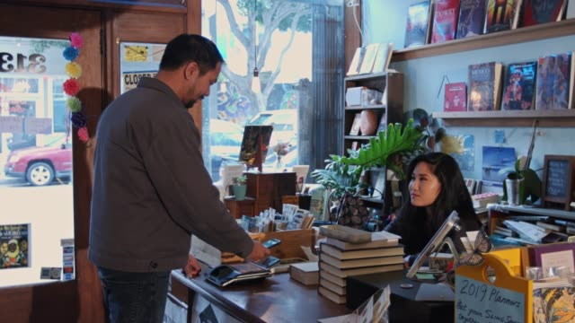 Man Buying Book with Mobile Payment on Cellphone
