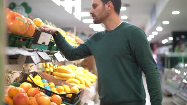 stockvideo's en b-roll-footage met man fruit in de supermarkt kopen. - tropisch fruit