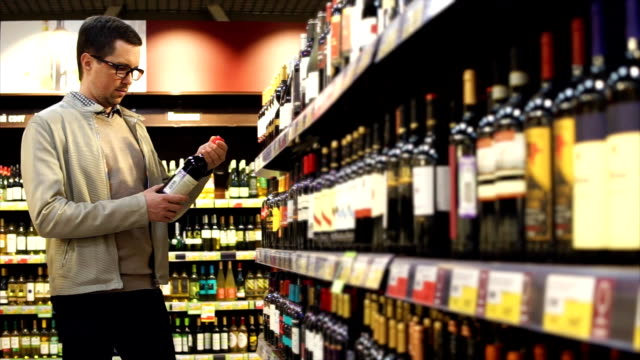 Man buying red wine in the liquor store video