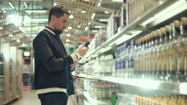 man buys alcohol in supermarket. - vodka video stock e b–roll