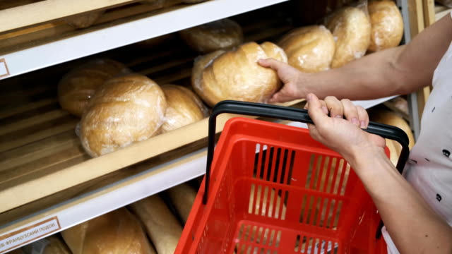 man buys bread in the mall. a young guy chooses bread and puts in a shopping cart. bread selection man buys bread in the mall. a young guy chooses bread and puts in a shopping cart. close-up bread selection bread stock videos & royalty-free footage