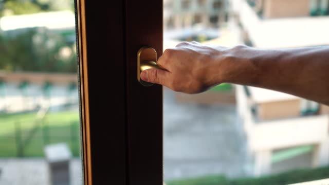 vídeos de stock e filmes b-roll de a man by the golden handle opens a brown plastic window. - obras em casa janelas