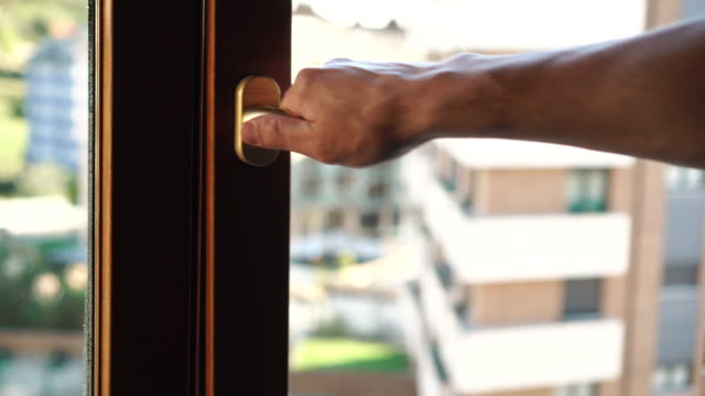 vídeos de stock e filmes b-roll de a man by the golden handle opens a brown plastic window - obras em casa janelas