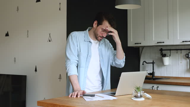 Man calculates personal finances feels stressed about bank overspend