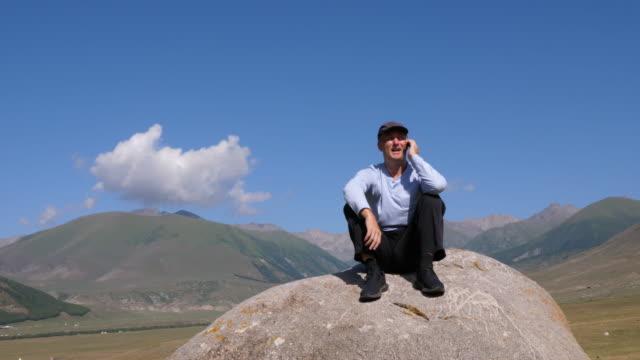 男子打電話時, 坐在石頭上與山后面 - 亞洲中部 個影片檔及 b 捲影像
