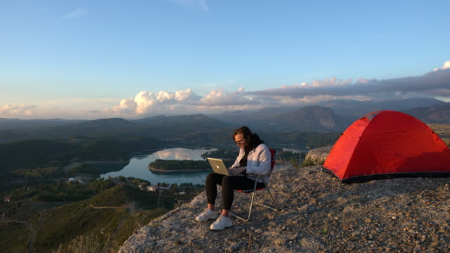 człowiek camping, gdzie internet i wolność spotykają - surfować po internecie filmów i materiałów b-roll