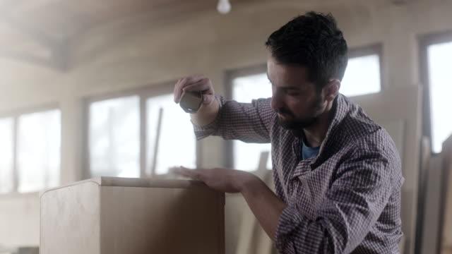 Carpintero de hombre usando papel de lija para acabado de trabajos sobre mueble - vídeo