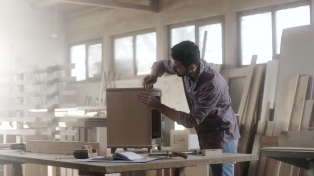 Man carpenter using sandpaper for finishing work on piece of furniture Man carpenter using sandpaper for finishing work on piece of furniture carpenter stock videos & royalty-free footage