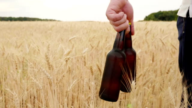 A man carries two bottles of cold beer over a field of barley. The concept is to quench your thirst. Slow motion video video