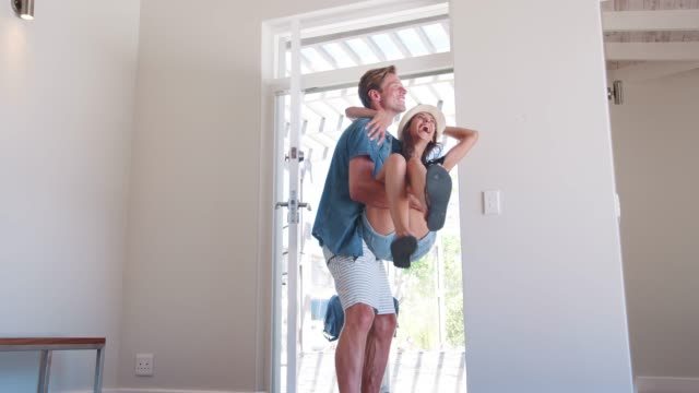 Man Carries Woman Over Threshold Of Honeymoon Rental Man carries new bride over the threshold of honeymoon accommodation - shot in slow motion newlywed stock videos & royalty-free footage