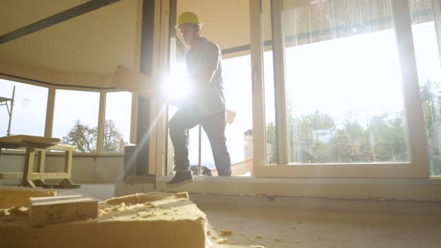 lågvinkel man som bär en stock in i huset resor på tröskeln och droppar stocken - solar panel bildbanksvideor och videomaterial från bakom kulisserna