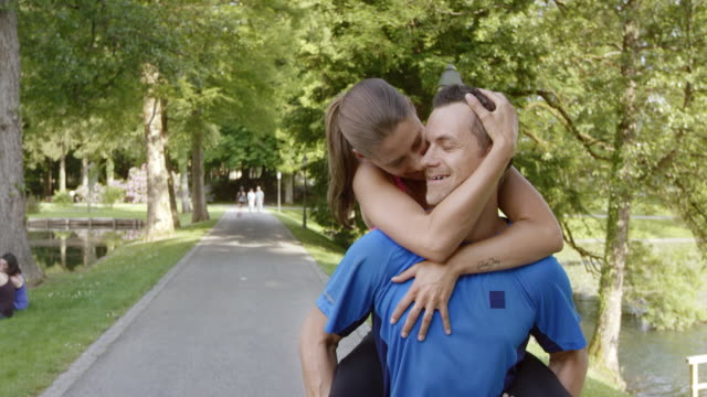 SLO MO TS Man carrying his woman on his back in a park video