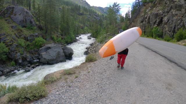 man carrying kayak up riverside road slow motion - alaska stato usa video stock e b–roll