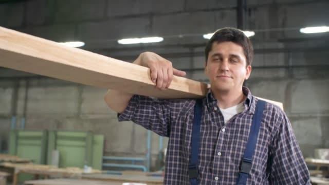 Man Carrying Plank along Carpentry Shop