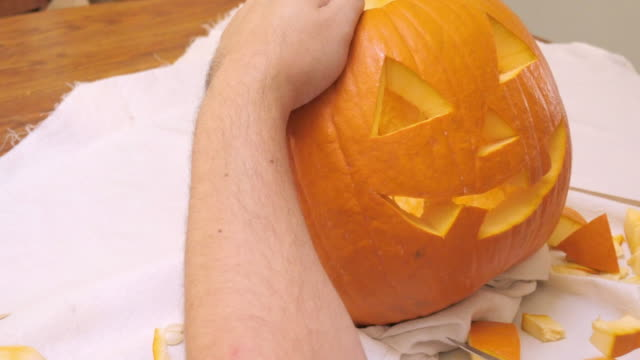 man carves a mouth in a jack 'o' lantern - incisione oggetto creato dall'uomo video stock e b–roll
