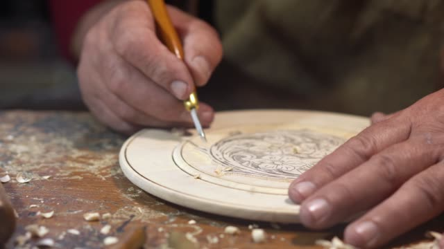 man carving decorative wall plate - prodotto d'artigianato video stock e b–roll