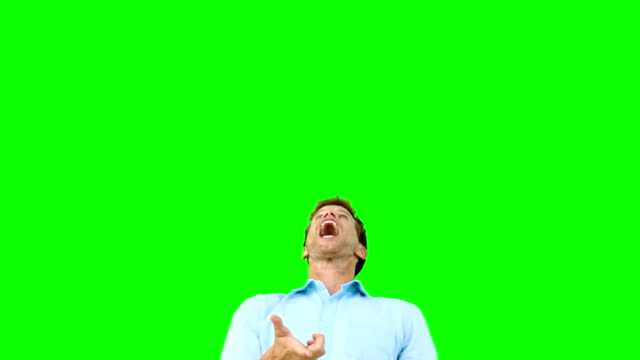 Man catching an orange segment with mouth on green screen video