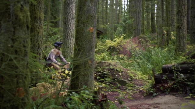 活気に満ちた緑の森のダートマウンテンバイクで大きな空気をキャッチ男 ビデオ