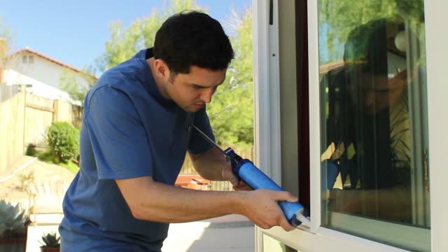 vídeos y material grabado en eventos de stock de hombre caulks cocina ventana - reparador