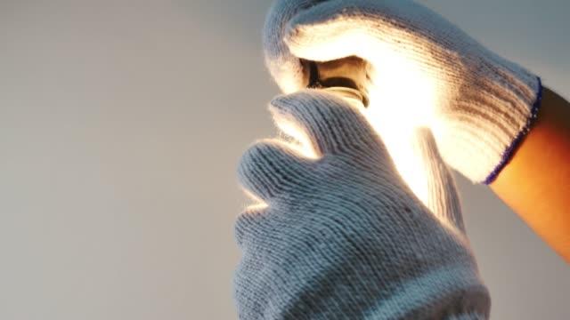 Man chaging lightbulb to led lamp