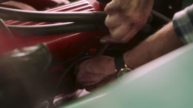 ein mann wechselt einen zündkerze in einem oldtimer - steckschlüssel stock-videos und b-roll-filmmaterial