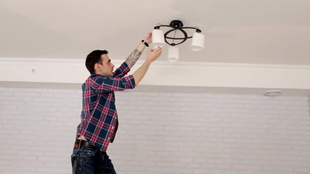 Man changes the light bulb in the chandelier standing on a ladder.