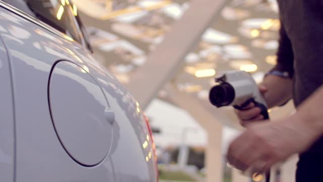 vídeos de stock e filmes b-roll de man charging its electric car - carregar