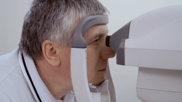 Man check his eyesight with modern optical equipment Doctor check eyesight of senior man with modern equipment. Old man look on the oculist and don't move his eyes. Diagnostic eyesight of pensioner. eye exam stock videos & royalty-free footage