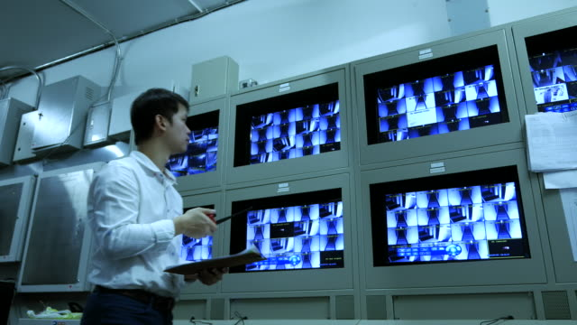 Man Checking at monitors of security surveillance system video