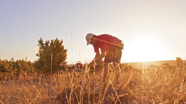 ds man kontrollera drone på kulle vid solnedgången - endast en medelålders man bildbanksvideor och videomaterial från bakom kulisserna